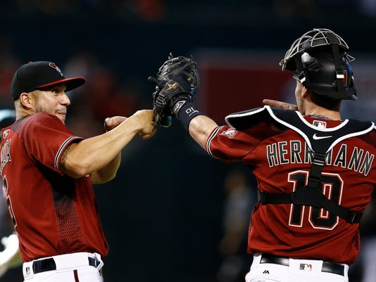 Arizona Diamondbacks' David Peralta, left, and Chris Herrmann (10) celebrate their victory after a baseball game against the Milwaukee Brewers Sunday, June 11, 2017, in Phoenix. (AP Photo/Ross D. Franklin)