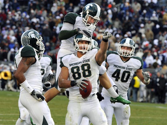 MSU's Brian Linthicum (88), Aaron Bates, top, and the rest of the  Spartans celebrate after Linthicum recovered a Penn State onside kick to seal the Spartans' Big Ten Championship-clinching 28-22 victory on Nov. 27, 2010.
