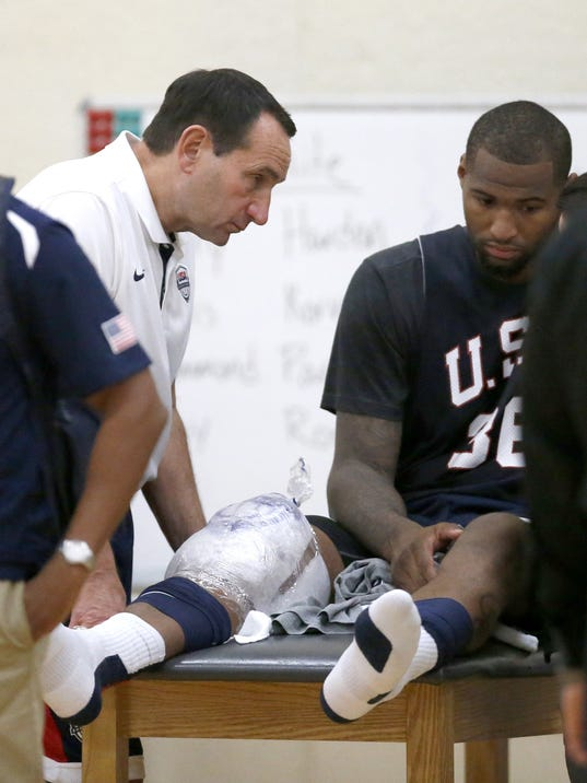 USA head coach Mike Krzyzewski talks with injured DeMarcus Cousins after a practice of the men's U.S. National basketball team Thursday, Aug. 14, 2014, in Chicago. The U.S. team will face the Brazilian team in an exhibition game at the United Center in Chicago Saturday. (AP Photo/Charles Rex Arbogast)