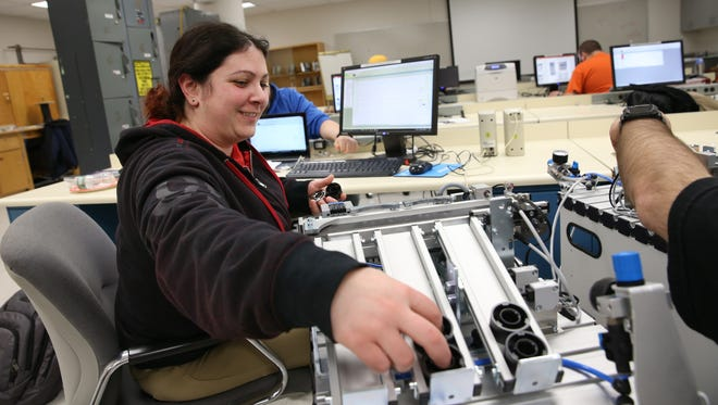 Elena Kern of Farmington removes pucks from the chute of a miniature assembly line  as she works on a computer program to control the machine's ability to sort items at a MCC mechatronics class,.held at Kodak Business Park in Rochester Tuesday, March 21, 2017.