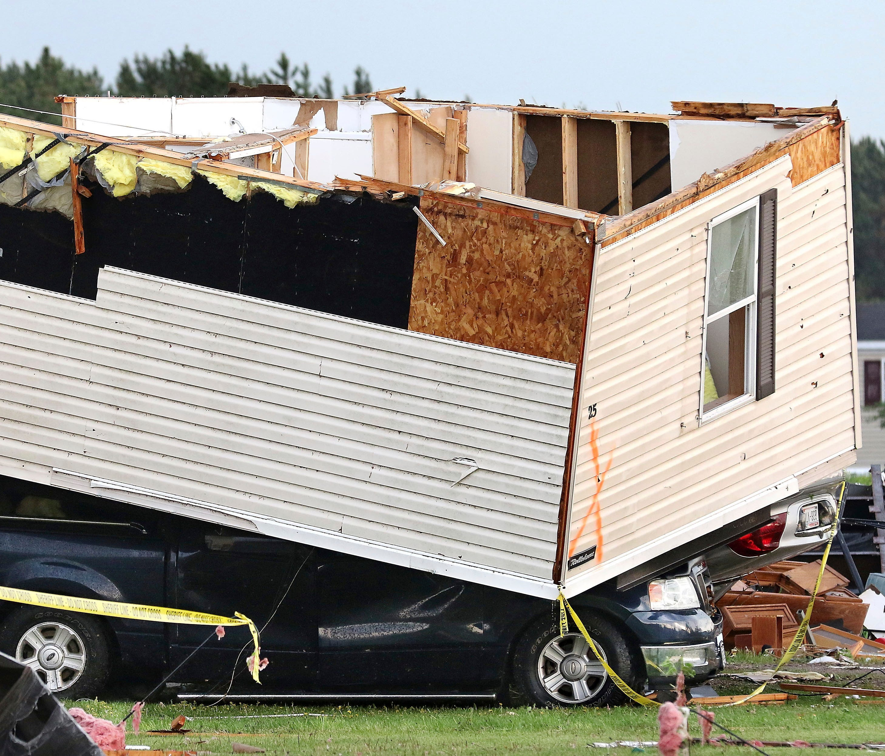 Part of a building sits on a vehicle after a tornado ripped through Prairie Lake Estates trailer home park, just north of Chetek, Wis., Tuesday, May 16, 2017.