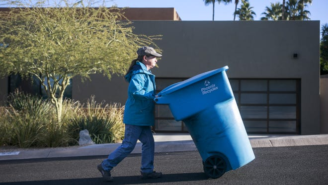 Phoenix resident Mary Westheimer wheels her empty recycling container back home. The city has launched a recycling-rewards partnership with Recyclebank, an eco-friendly marketing company that has developed a custom app and website to teach residents to reduce waste and sort their trash.