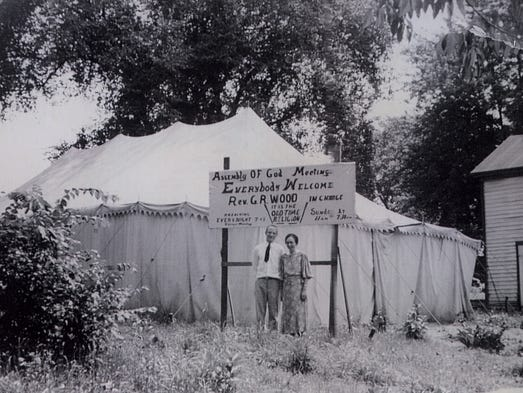 George Roy Wood and wife Elizabeth stand in front of a tent where he conducted meetings at Ravenna, Ohio, in 1938. The family jokes that â??Rev. G.R. Wood in chargeâ? is typical of the man who inspired his son and grandson, who also entered the ministry.