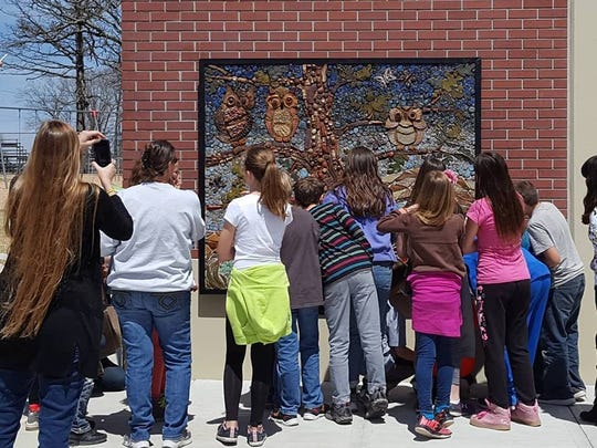 Highlandville students admire their mosaic artwork.