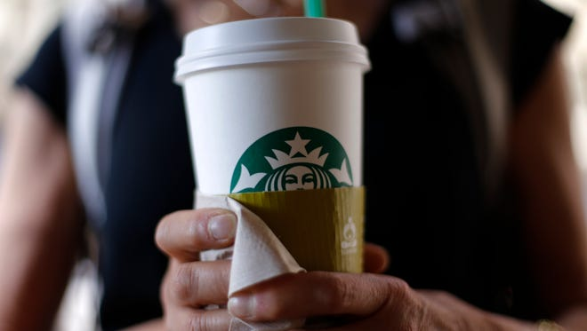 A woman holds a coffee drink outside a Starbucks in downtown Chicago.