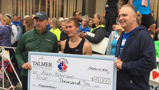 Bessemer's Alan Peterson, middle, receives the giant check for winning the 39th Detroit Free Press/Talmer Bank Marathon on Oct. 16, 2016.