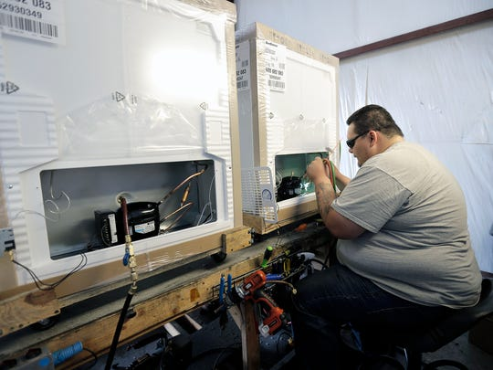 Worker Alex Galarza installs a compressor in a low-energy refrigerator at the SunDanzer El Paso factory and distribution center in Northeast El Paso.