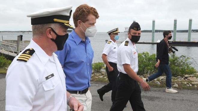 Michael Burns, left, director of the Center for Maritime and Professional Training at Massachusetts Maritime Academy, guides U.S. Rep. Joseph P. Kennedy III along the waterfront Friday during a visit to the campus.