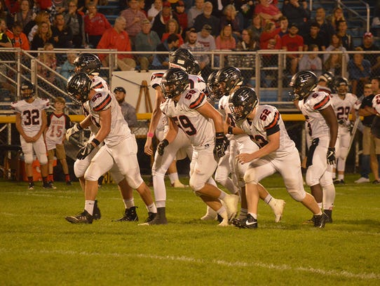 Pleasant's offensive line break the huddle during a