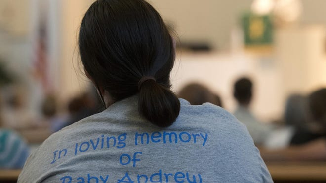 A family member listens during a service to remember and honor National Pregnancy and Infant Loss Awareness Day. The service at St. Paul's Methodist Church, was followed by a candle-lit walk around Lake Ella. This year's walk is Thursday, Oct. 10.