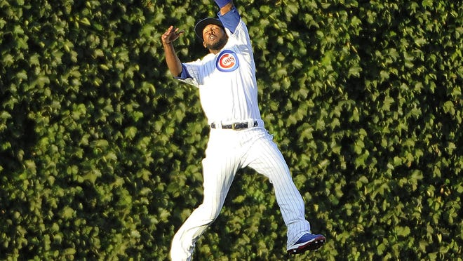 AP Chicago Cubs center fielder Dexter Fowler catches a ball hit by San Francisco Giants? Angel Pagan during an August baseball game at Chicago?s Wrigley Field. FILE - In this Aug. 6, 2015, file photo, Chicago Cubs center fielder Dexter Fowler catches a ball hit by San Francisco Giants' Angel Pagan during the first inning of a baseball game in Chicago. Wrigley Field is a ballpark that while viewed as a throwback today has in fact played a big role in changing the way fans view sports. It was the first to let them keep foul balls. It was the first with organ music. And it was the first to be cleaned up in an effort to attract women and children. These are just some of many characteristics that sets the fabled stadium apart, along with the famed marquee, the manual scoreboard, the ivy-covered brick outfield walls and the ballhawks in the surrounding streets chasing home runs. (AP Photo/David Banks)
