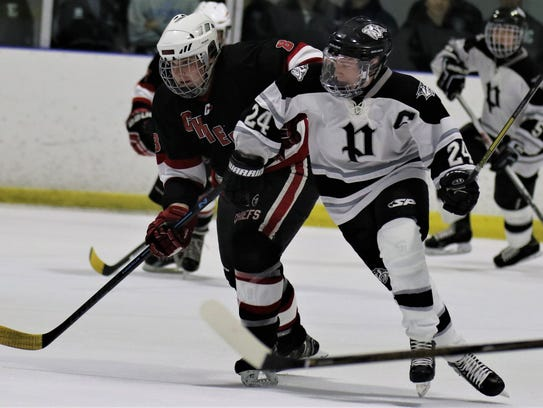 Battling for a loose puck Wednesday night are Canton's