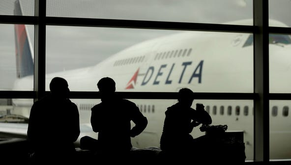Delta Air Lines travelers wait Oct. 29, 2012, for flights,