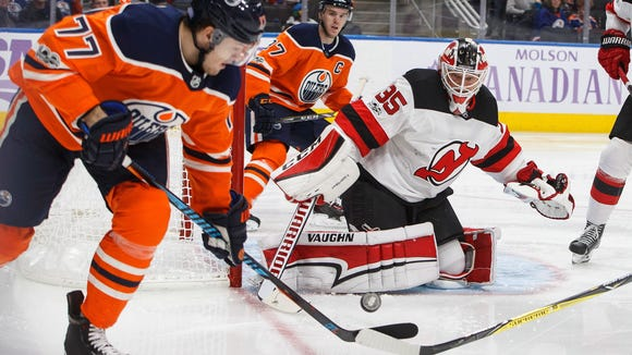 New Jersey Devils goalie Cory Schneider (35) makes a save as Edmonton Oilers' Oscar Klefbom (77) picks up the rebound during second-period NHL hockey game action in Edmonton, Alberta, Friday, Nov. 3, 2017. (Jason Franson/The Canadian Press via AP)