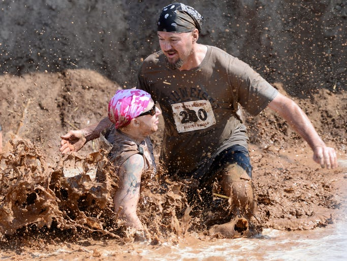 Sharon Rusch and George Buerman of Shawano collide after going down an incline into a pool of muddy water at the finish of the Hot Mess Mud Run in Greenleaf, Wis. on Saturday, Aug. 9, 2014. Kyle Bursaw / Press-Gazette Media