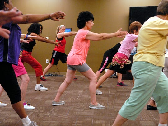MIchelle Kramer, center, stretches at the end of the Zumba Gold class at the Humana Guidance Center on Hikes Lane.