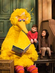 In this April 10, 2008, file photo, Big Bird reads to Connor Scott and Tiffany Jiao during a taping of Sesame Street in New York.