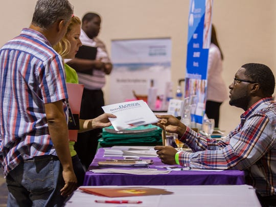 From right, Jackie Beard, an enrollment specialist at Florida SouthWestern College, speaks with Joan Garcia and David Guatarasma during a job fair at Harborside Event Center in Fort Myers. The largest career fair to occur in Southwest Florida in some time is coming to FGCU's Alico Arena on May 3.