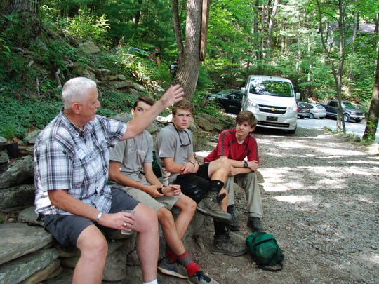 Joe Avery, left, recounts his time as part of the first N.C. Outward Bound class in 1967 to a group of current students during a reunion July 13 at Table Rock Base Camp.
