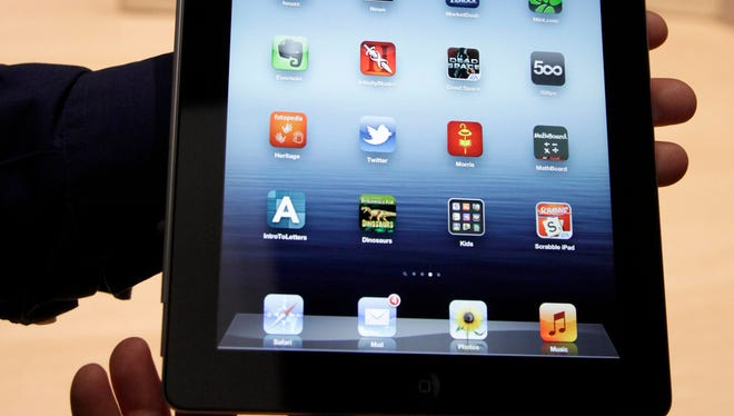 An Associated Press reporter holds up the new iPad during an event in San Francisco, Wednesday, March 7, 2012. T