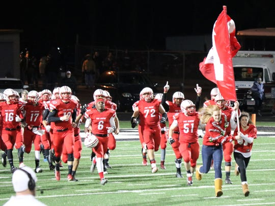 The Port Clinton football team takes the field in Tiffin for a playoff game against Columbus Bishop Hartley.