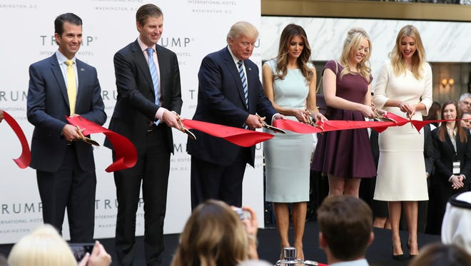 Then-presidential candidate Donald Trump, together with his family, from left, Donald Trump Jr., Eric Trump, Trump, Melania Trump, Tiffany Trump and Ivanka Trump, cut the ribbon during the grand opening of Trump International Hotel in Washington on Oct. 26, 2016.