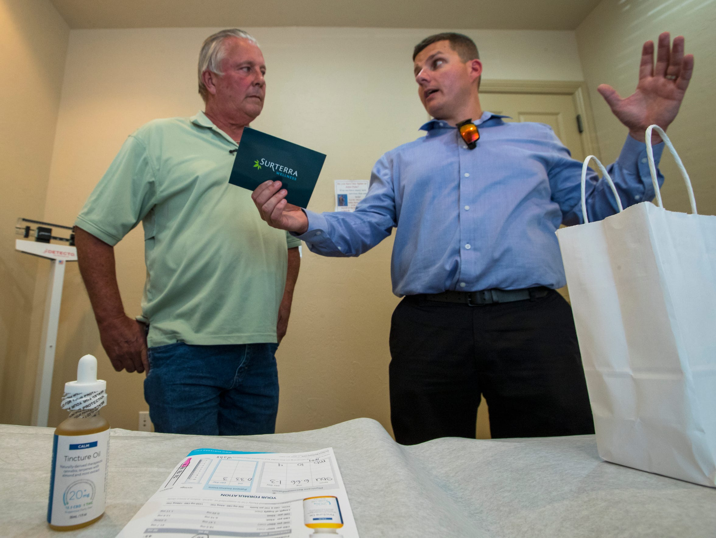 Allen Bills, left, a medical marijuana patient, discusses the details of his medication order with Matthew Lipani, an assistant manager with Surterra Inc. Surterra, a medical marijuana distributor, provides delivery services to patients unable to visit their store locations.