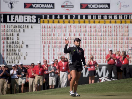Ariya Jutanugarn waves to the crowd after sinking her