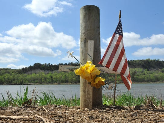 A cross and flag in memory of Alicia Marie Hummel sits