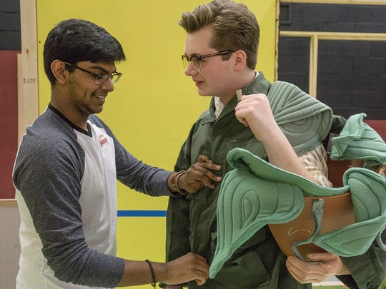 Anirudh Keshamouni, the voice of the plant, helps Seymour Dalton Barthold suit up for a scene.