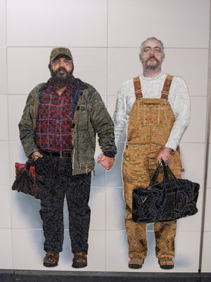 This Nov. 29, 2016 photo provided by the New York Metropolitan Transportation Authority shows a mural by Vik Muniz on the wall of the Second Avenue subway station at 72nd Street in New York. The subjects are Thor Stockman, left, and his husband, Patrick Kellogg.