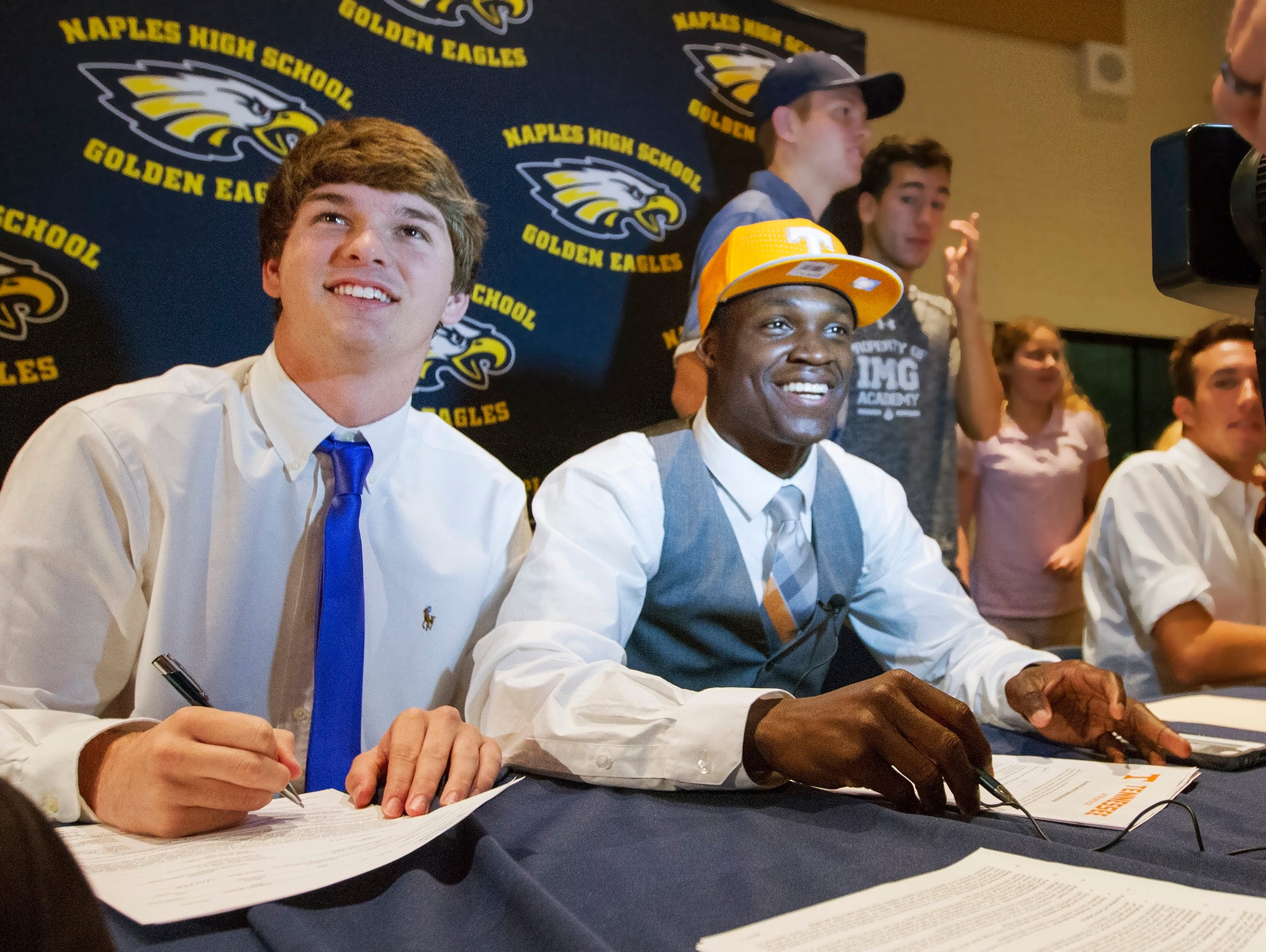 Naples High School football players Chris Riley, left, and Carlin Fils-aime, center, were among the school's athletes who signed National Letters of Intent Wednesday at the school. Riley is going to the College of the Holy Cross and Fils-aime to the University of Tennessee.