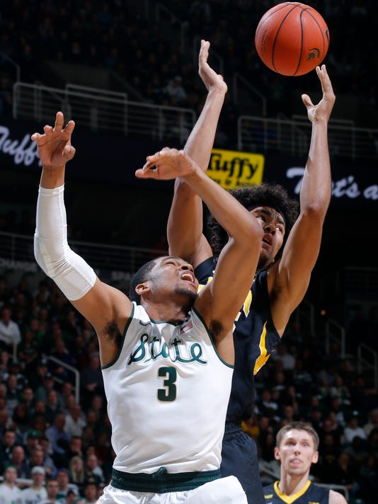 Michigan State's Alvin Ellis III (3) and Iowa's Dom Uhl reach for a rebound during the first half of an NCAA college basketball game Thursday, Jan. 14, 2016, in East Lansing, Mich. (AP Photo/Al Goldis)