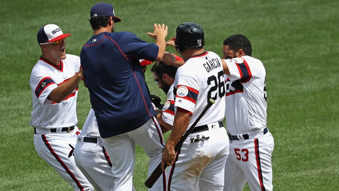 Players mob Adam Eaton of the Chicago White Sox (center) after he got the game winning hit, a single in the 9th inning, against the Detroit Tigers in a game suspended by rain last night at U.S. Cellular Field on July 24, 2016 in Chicago, Illinois.
