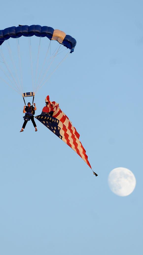 Dan Spisak parachutes into Howard Wood Field with an American flag before the 2014 Dakota Bowl game at Howard Wood Field.