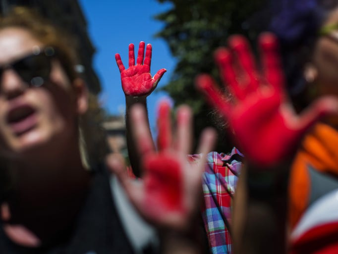 Demonstrators show their hands painted with red paint as they protest against the Israeli army's bombings in the Gaza strip during a protest in Barcelona, Spain, Thursday, July 31, 2014. Israel said Thursday it has called up another 16,000 reservists, allowing it to potentially widen its Gaza operation against the territory's Hamas rulers in a war that has killed more than 1,300 Palestinians and more than 50 Israelis.  AP Photo/Emilio Morenatti)
