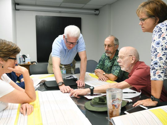 Ken Putnam, center, director of the city's transportation department, and Assistant City Manager Cathy Ball, far right, look over I-26 Connector plans with Asheville City Councilwoman Julie Mayfield, far left, and two citizens, Bruce Emory and Dave Nutter.