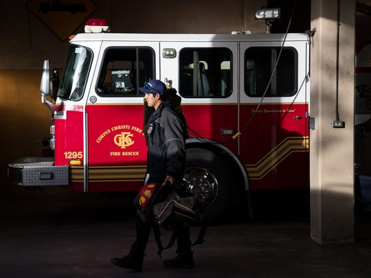 Corpus Christi Firefighter Adam Hernandez caries his bunker gear to engine 1 in Fire Station 1 at the start of his shift on Friday, Jan. 26, 2018.
