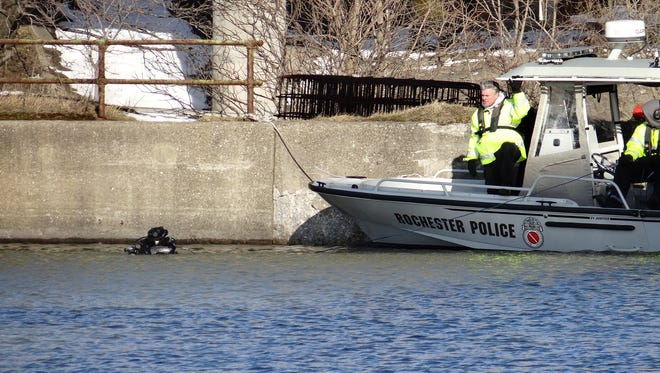 A police scuba diver confers with a crew member shortly before recovering a body from the Genesee River late Sunday afternoon.