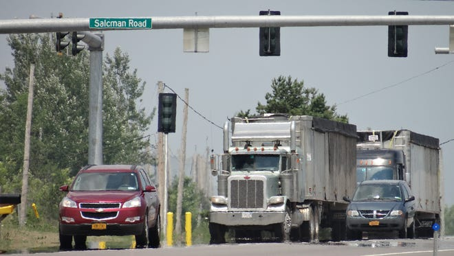 Waste-hauling trucks head for Seneca Meadows Landfill on sun-baked Route 414 in Seneca County.