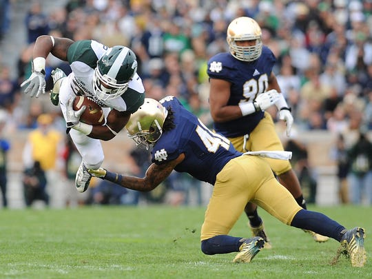 MSU running back Jeremy Langford is upended by Notre Dame's Matthias Farley during the Spartans' 17-13 loss on Sept. 21, 2013 in South Bend, Ind.