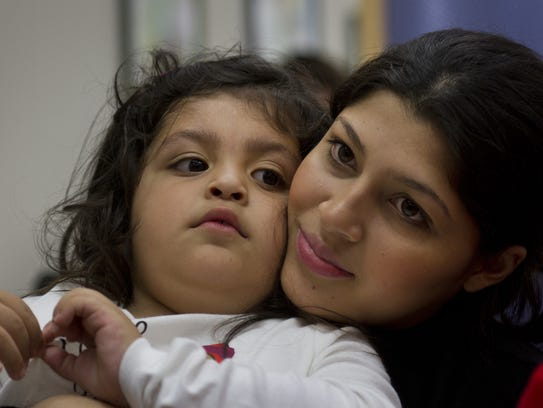 A 3-year-old sits quietly on her mother's lap at a