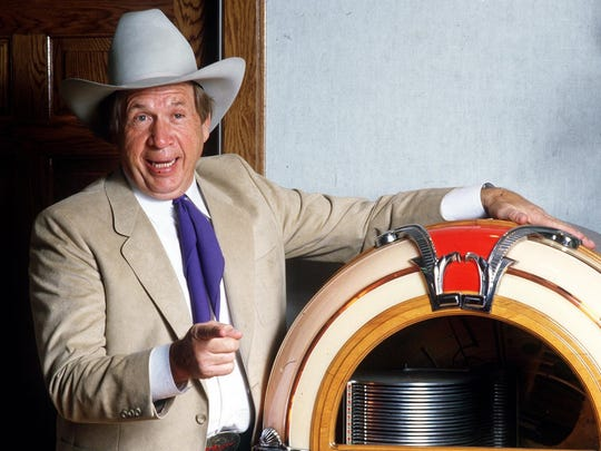 Country music star  Buck Owens (1929-2006) is pictured with a jukebox in the 1980s.