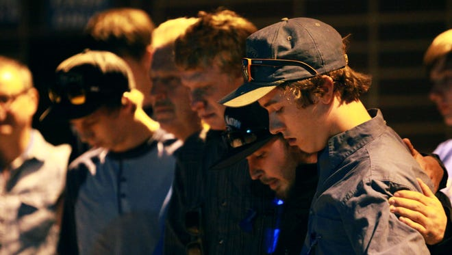 (From left to right) Kyle Strunk, Ken Strunk, JJ Perea, Brandon Holder and Troy Gilbreth embrace during the candlelight vigil held for Wesley Strunk at the Colorado State University Equine Center on June 27, 2017.