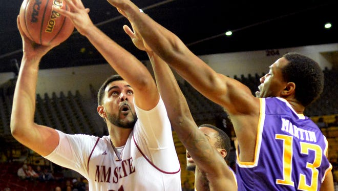 New Mexico State center Tanveer Bhullar goes up for a shot against Tennessee Tech's Ryan Martin on Tuesday at the Pan American Center.
