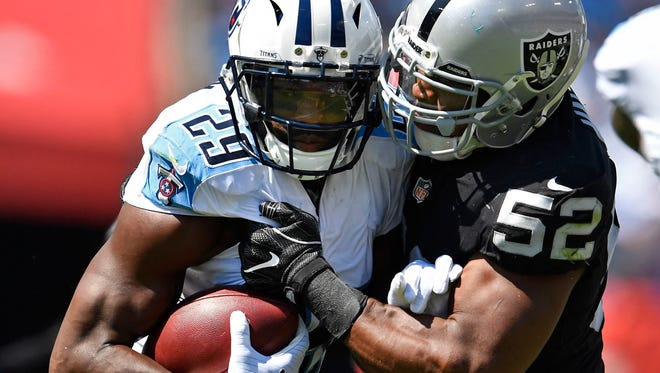 Tennessee Titans running back DeMarco Murray (29) runs while Oakland Raiders defensive end Khalil Mack (52) tries to tackle him in the third quarter at Nissan Stadium Sunday, Sept. 10, 2017 in Nashville, Tenn.
