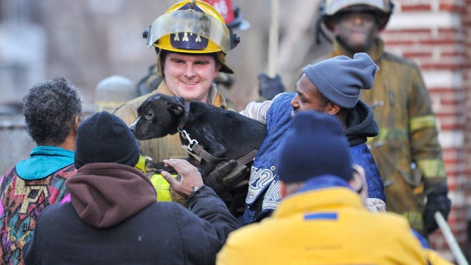 Trial fire fighter Jeff Brinker brings a dog out of the house that was burned a house fire near East Vernor in Detroit on Dec. 22, 2014.