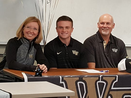 Community School senior Alex Murphey (center) signed a letter of intent to run track at Wake Forest during a ceremony at the school Wednesday, Nov. 15, 2017.