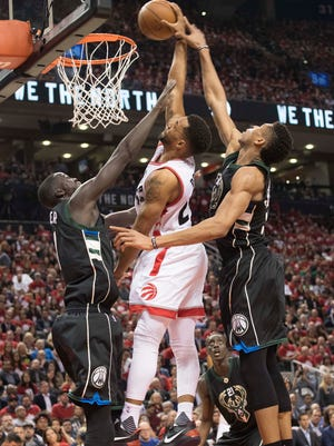 Raptors guard Norman Powell throws down a dunk between Bucks forward Giannis Antetokounmpo (right) and  Thon Maker on Monday.