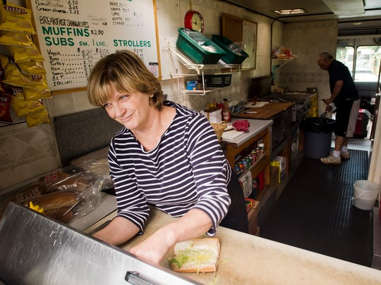 Pam Bissonnette of Pam's Deli food truck takes orders during the lunch rush, parked on University Place at the University of Vermont Tuesday, July 29, 2014. Pam and husband George have a decades-long history food trucking around the city.